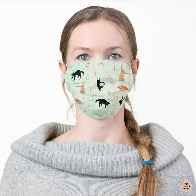 Woman wearing a green face mask with cat prints