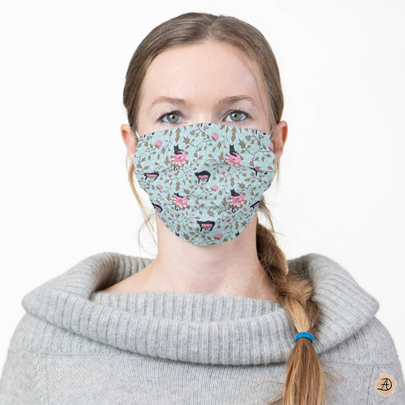 Woman wearing a face mask with a floral print with cute cats