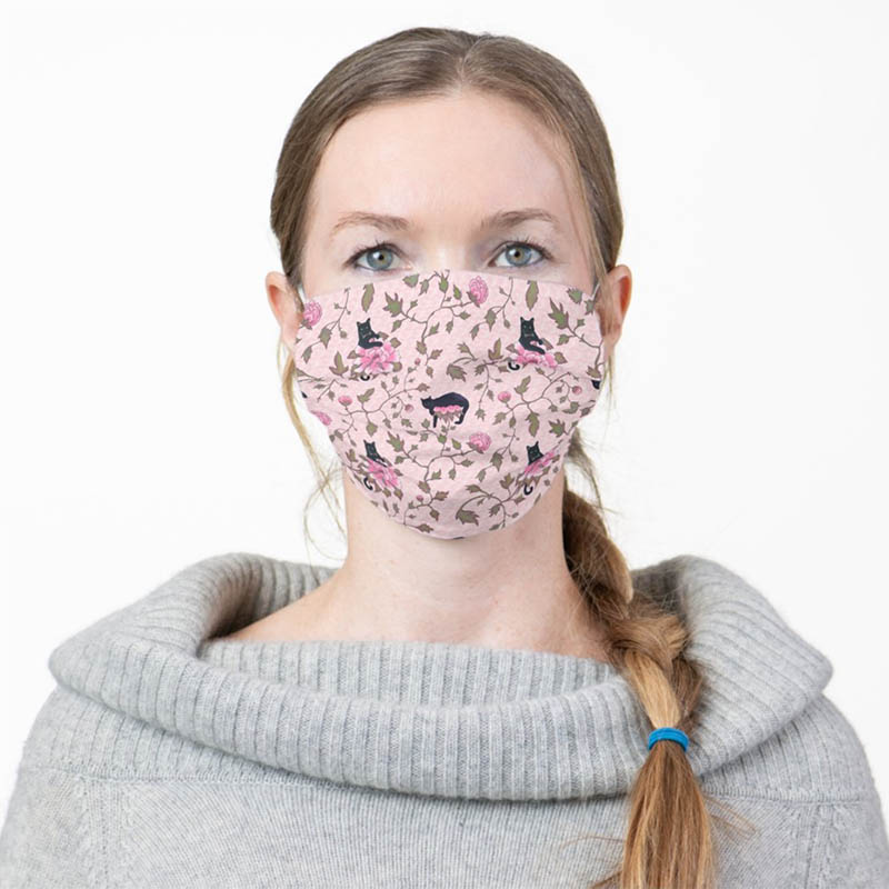 Cat lady wearing a face mask with her favorite black cats and pink peony flowers.