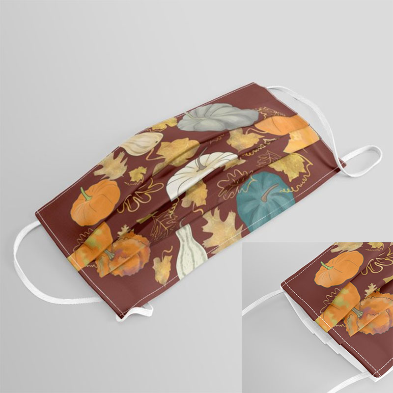 Cloth face covering with fall pumpkins prints over a rusty brown background