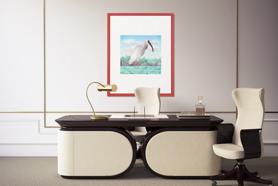 Office scene with red framed wall art depicting a crested ibis bird