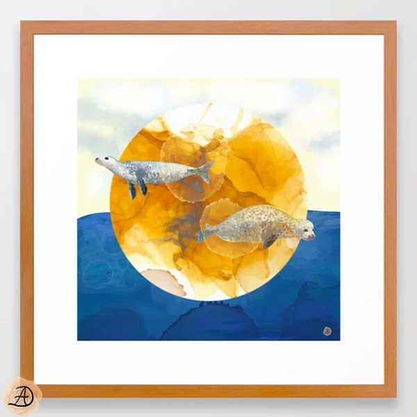 Coastal framed art depicting a surrealist scene with seals flying above a solar disc